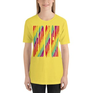 Woman with light brown shoulder length hair wearing black jeans & a yellow short sleeve t shirt which says head of gay in rainbow colours.