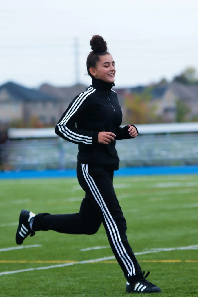 Female in dark tracksuit running on pitch