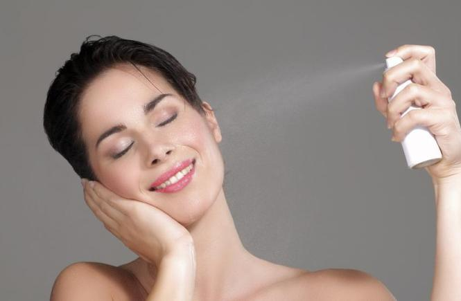 woman spraying facial mist on her face