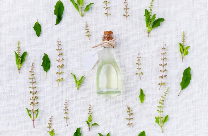 essential oil glass bottle and herbs