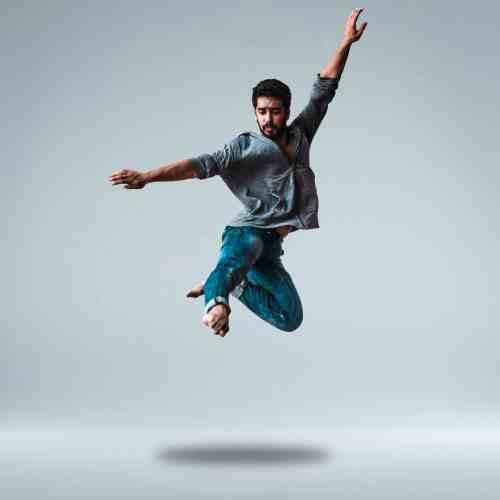 man-jumping-while-raising-his-both-arms-1701200