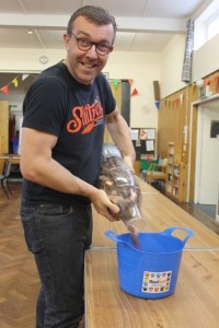 a man pouring the bottle of pennies into a bucket