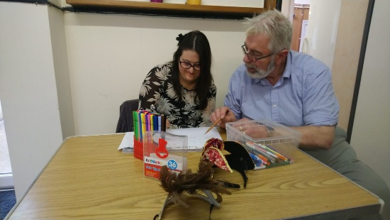 a woman is drawing with coloured pens and a man is sitting next to her looking at her work