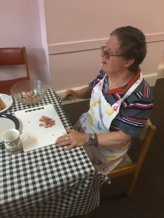 a person is sat at the head of the table with the black and white check table cloth. They are wearing an apron and chopping sausages