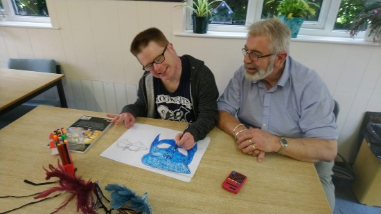 a man is drawing a blue face while sat at a table. A man with a beard is sitting next to him