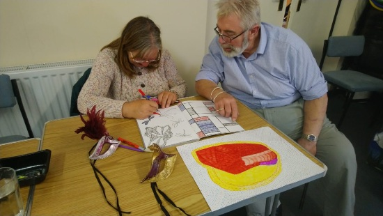 a woman in drawing in a big art book with coloured pens and a man with a beared is sat next to her watching