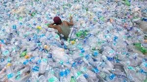 a person wades through piles and piles of waste plastic