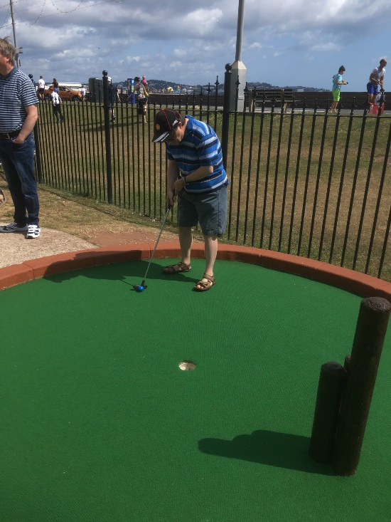 a man in a stripy top is putting towards the hole on a crazy golf course