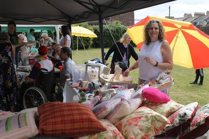a woman prepares a stall full of crafts and furnishings