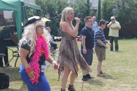 singer in a leopard print dress lines up with dancers - on a a blond wig and feather boa, one in blue shorts and a blue t-shirt and one in brow shorts a stripy shirt and baseball cap