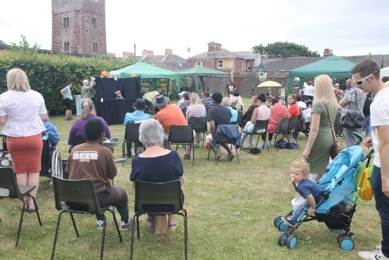 People sitting in a field watching a puppet show