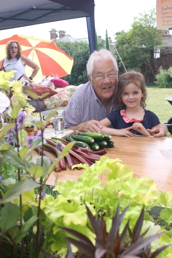 a man and a young girl look at plants and rhubarb and courgettes on a table