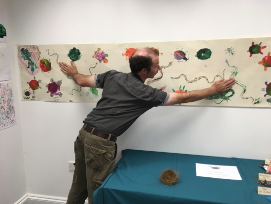 a long picture is up on the wall as a man counts the snakes and terrapins it includes
