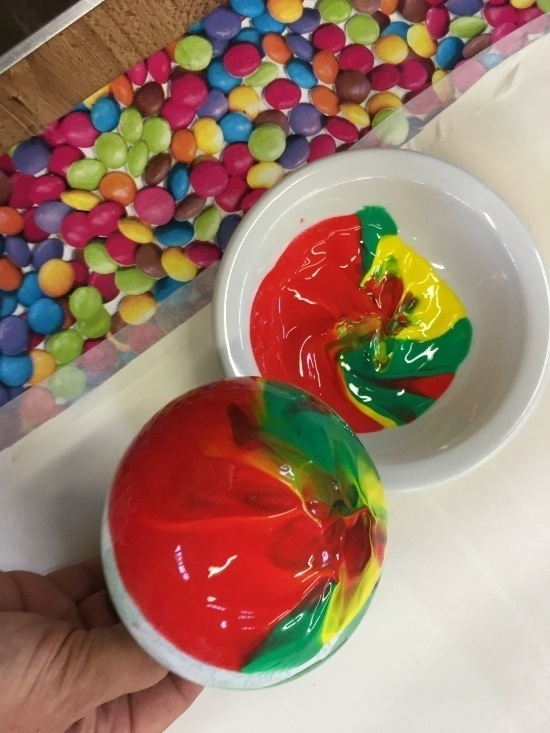 two pots of colourful paint of red, green and yellow