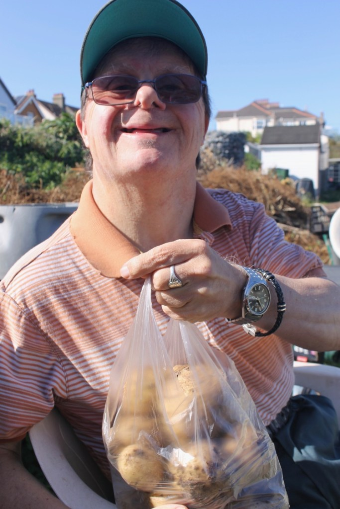 a man is holding a bagful of freshly dug potatoes