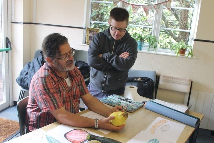 a man with a beard is still at a table with drawings of fruit. He is holding a big pear and examining it. Stood next to him with his arms folded, listening is a younger man
