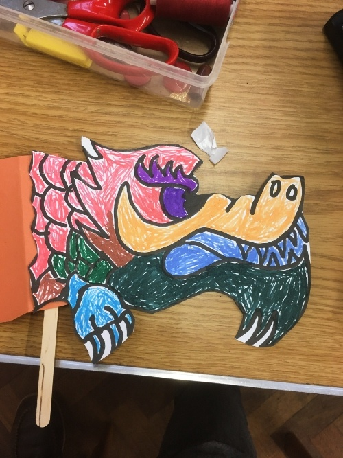 a chinese dragon made of paper with a purple crepe paper middle and sticks at the bottom