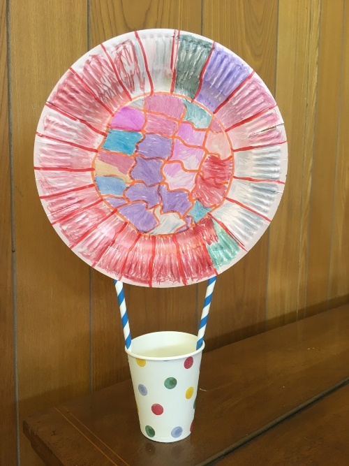 a paper cup stuck with straws to a paper plate facing out like a ball. Both have been coloured in a multi-coloured design to look like a hot air balloon