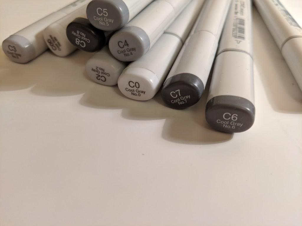 Copic cool grey pens strewn across a desk