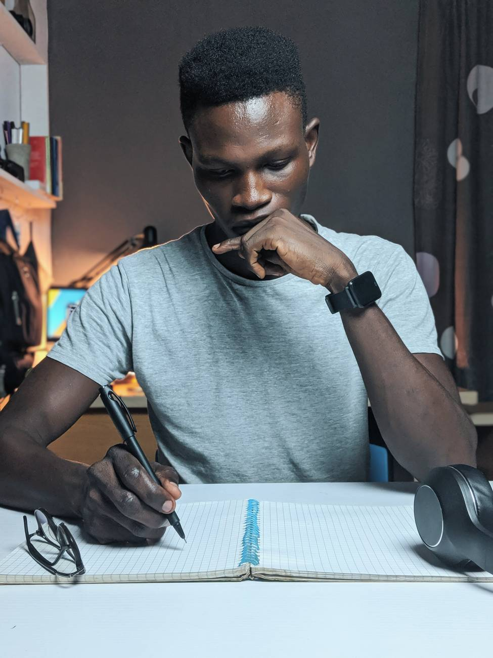 photo of man writing on notebook. Writing well to improve traffic to your blog