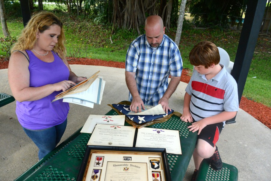 Meghan Burns, Jeremy Teitler and Conner Burns looking through the items that they found in their attic at Veteran's Park in Coral Springs