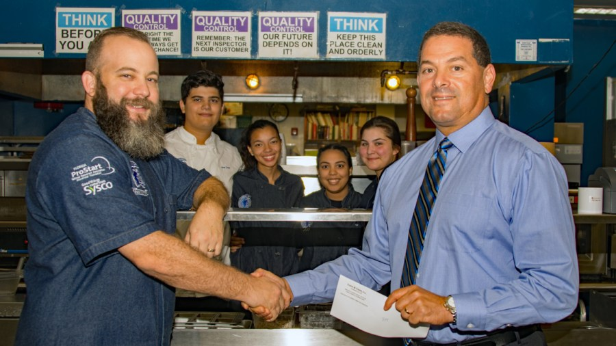 Scott Goodman, Culinary & Hospitality Instructor receives a check from Broward County Commissioner Michael Udine.