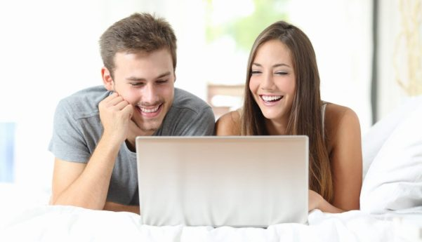 Couple watching videos on a laptop at home