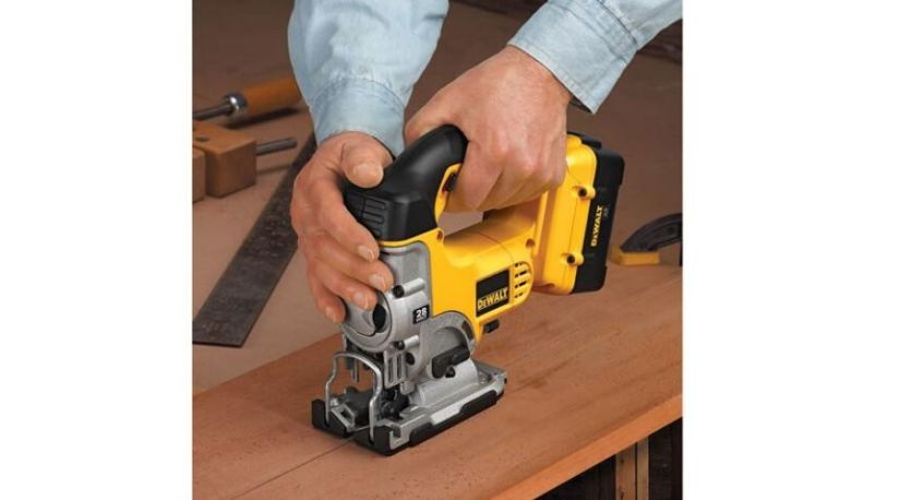 A person using best cordless jigsaw on a wooden surface