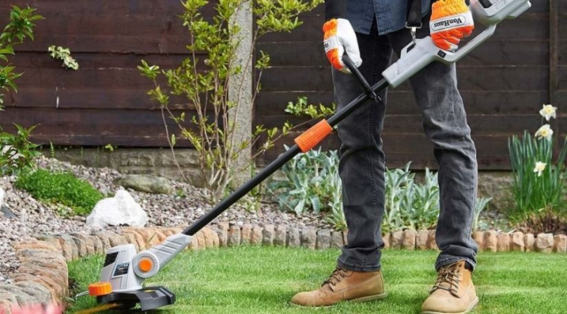 A man using the best cordless string trimmer to reduce an trim grass and other forms of weed in a lawn/garden