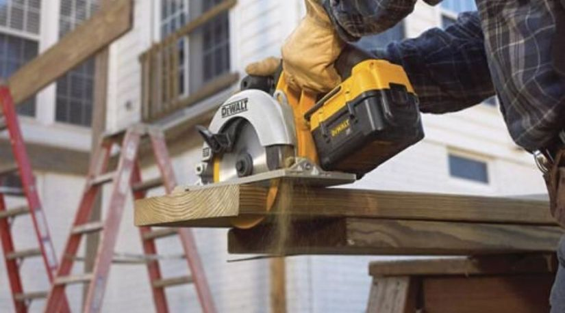 A man using the best cordless circular saw to cut through a wooden material