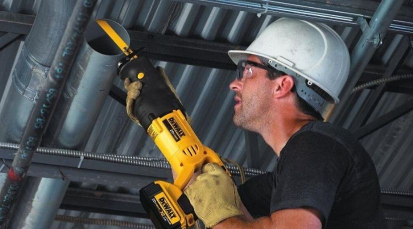 A man using the best cordless reciprocating saw to cut through and trim a metal material during construction work