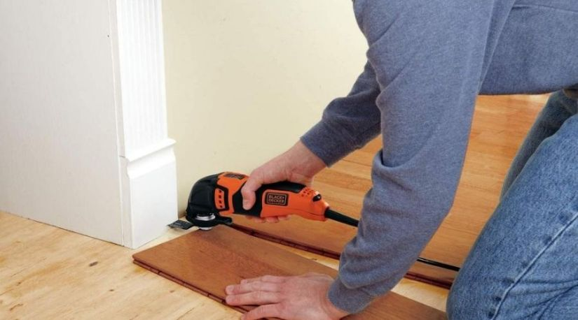 A woodworker using the best cordless oscillating tool to cut through a wooden material