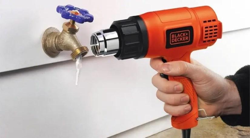 A plumber using the best cordless heat gun on a water tap
