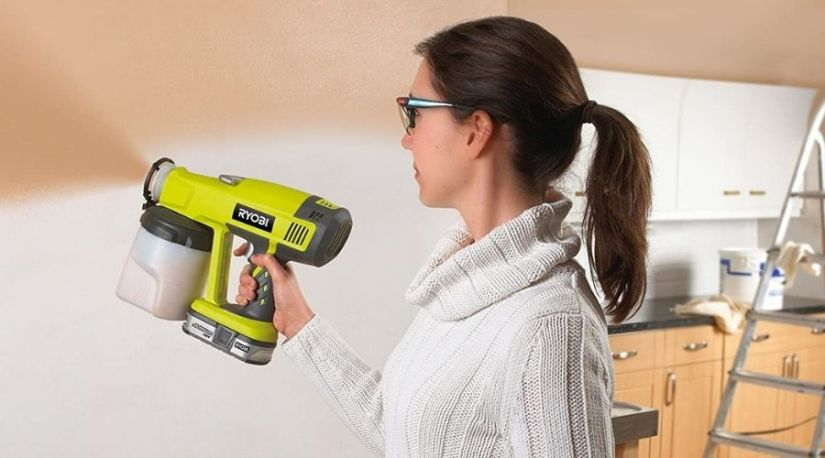 A pictorial representation of a lady using a model of the best cordless paint sprayer to spray the inner walls of the room