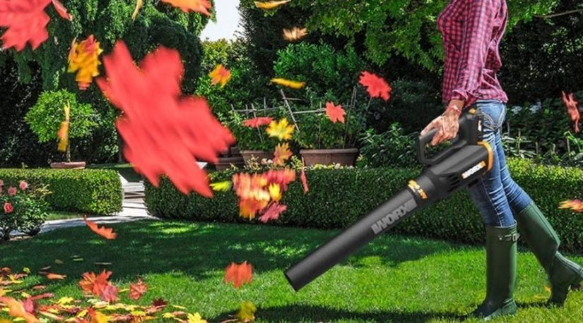 A woman using WORX WG547 20V (2.0Ah) Power Share Cordless Turbine Blower, one of the best cordless leaf blower under $100 to blow leaves in patio
