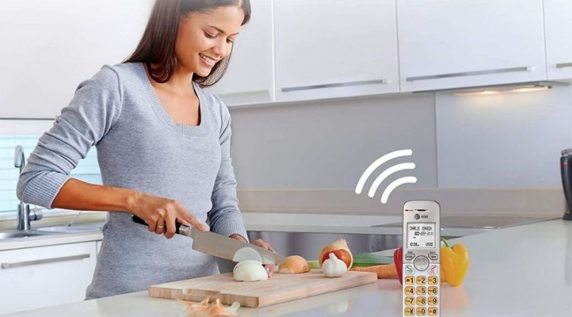 How to Block Calls on a Panasonic Cordless Phon. The picture gives a representation of a lady using a phone while cooking and on a call. With a call block system, she can be sure not to be interrupted with the unnecessary calls.
