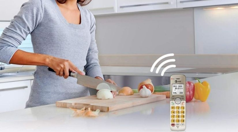 The image above displays a lady doing kitchen chores while simultaneously using the AT&T EL52313 3-Handset Expandable Cordless Phone, one of the best at&t cordless phone models. The simulated full-duplex handset speakerphone is allowing her to conduct a handsfree conversation thus enabling multitasking.