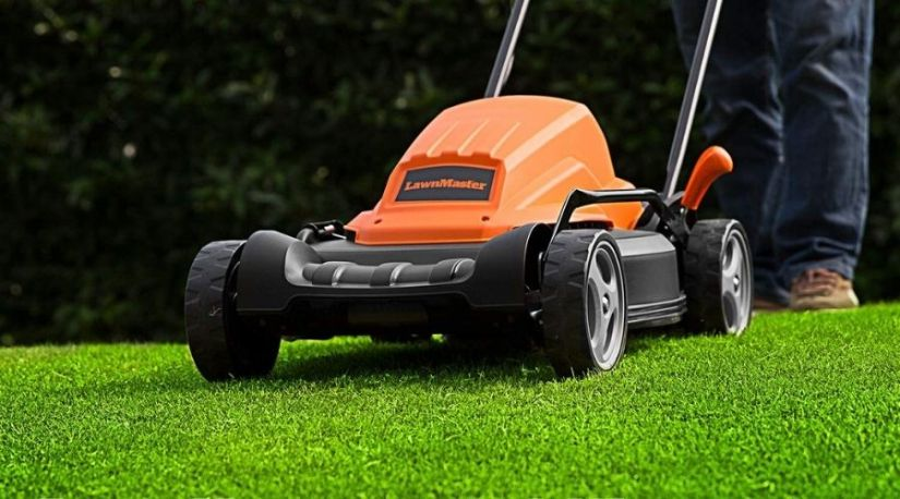 the picture shows a man using LawnMaster ME1218X Electric Lawn Mower 12AMP 19-Inch, one of the best lawn mower units to trim his lawn