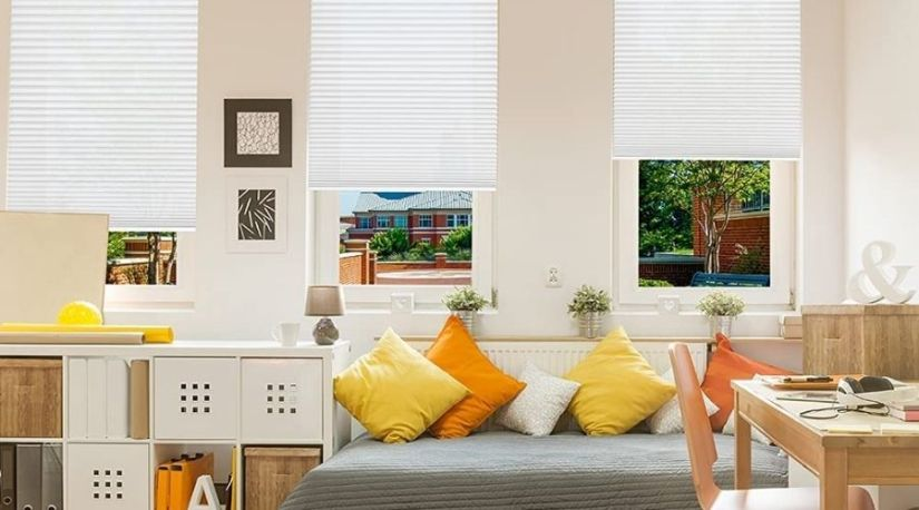 An image of Redi Shade Easy Lift Trim-At-Home Cordless Pleated Light Filtering Fabric Shade showing how the best cordless blinds allows for light in the living room, while also controlling the privacy of individuals