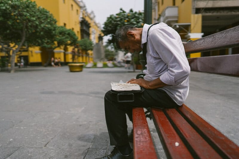 man sitting on a bench slouching with poor posture needs corechair