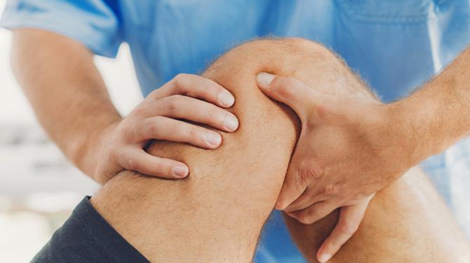 orthopedic doctor examining bent knee