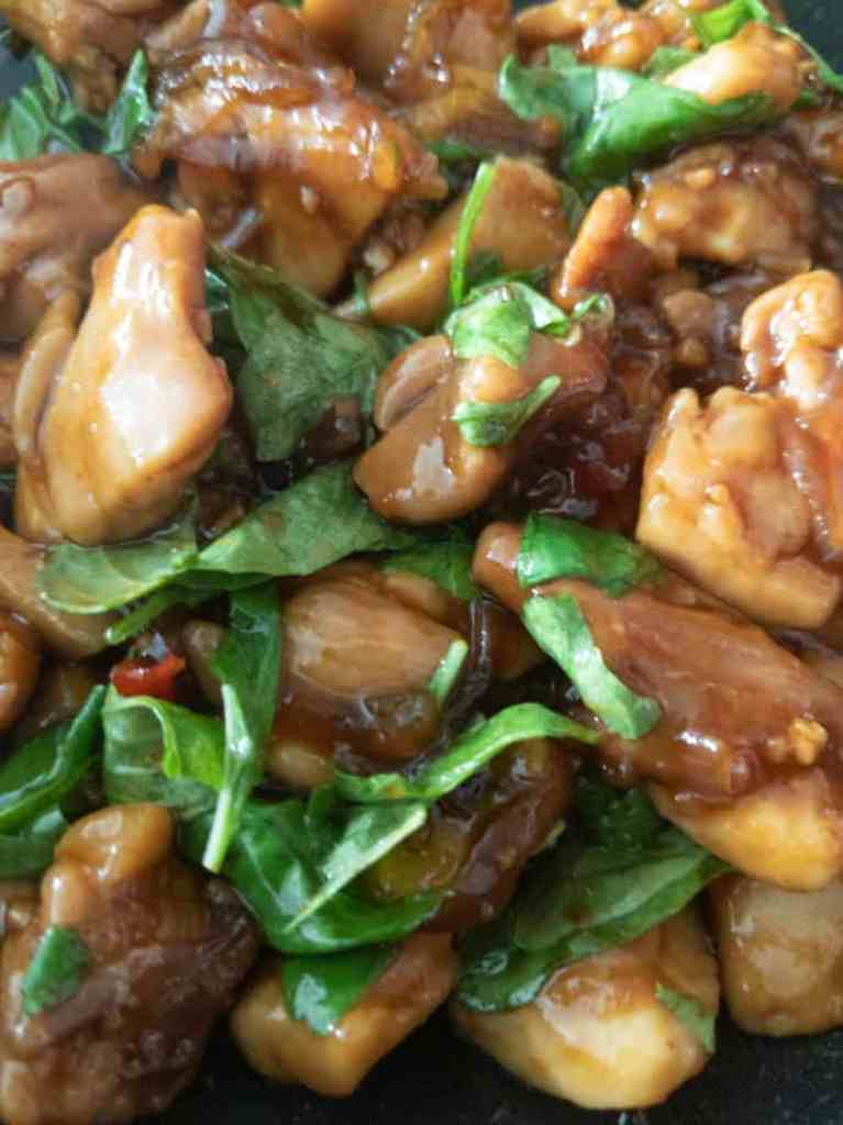Thai basil leaves are folded into the chicken stir fry after the pan has been removed from the heat.