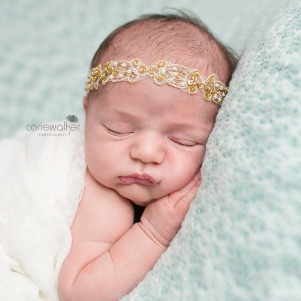 beautiful newborn girl with gold headband