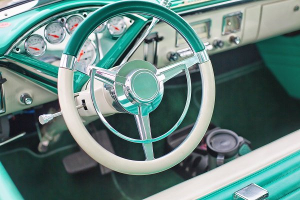 A turquoise and white steering wheel of a classic car. Image by Jill Wellington from Pixabay