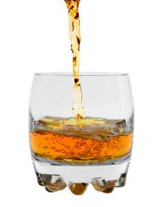 stream from a bottle of whisky is poured in a glass, isolated on a white background