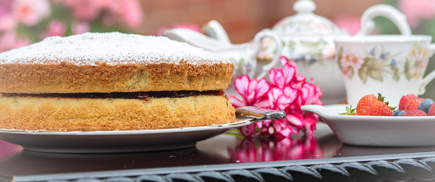A photo of a homemade Victoria sponge cake with fresh fruit and a pot of tea