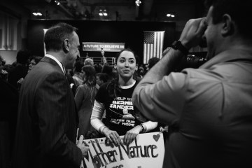 """A woman at the rallies carries a sign reading, """"Mother Nature Endorses Bernie."""""""