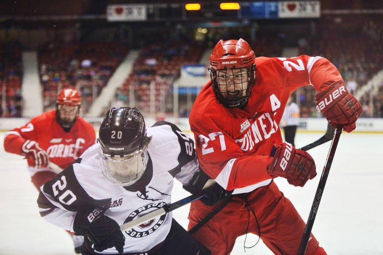 Senior Defenseman Patrick McCarron fights for the puck during the Red's Friday night match against Union in Lake Placid. (Cameron Pollack / Sun Photography Editor)
