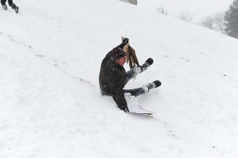Sliding down Libe Slope, Alex Ciampaglia '20 tries to hang on to his makeshift cardboard sled.