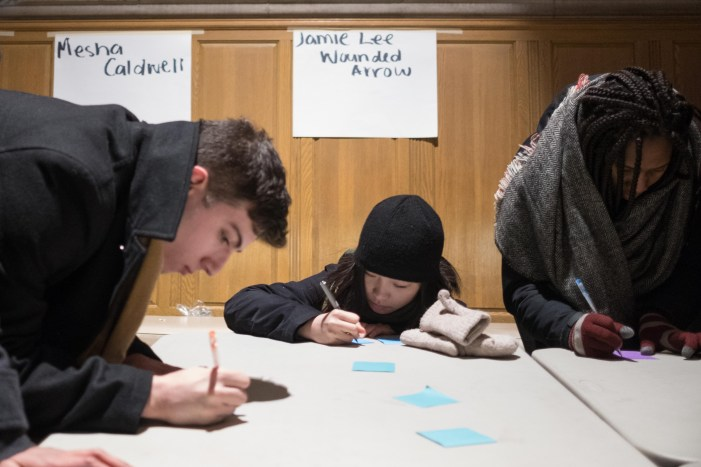 Demonstrators writing messages for victims at the Vigil for Transwomxn at Willar Straight Hall on Wednesday.